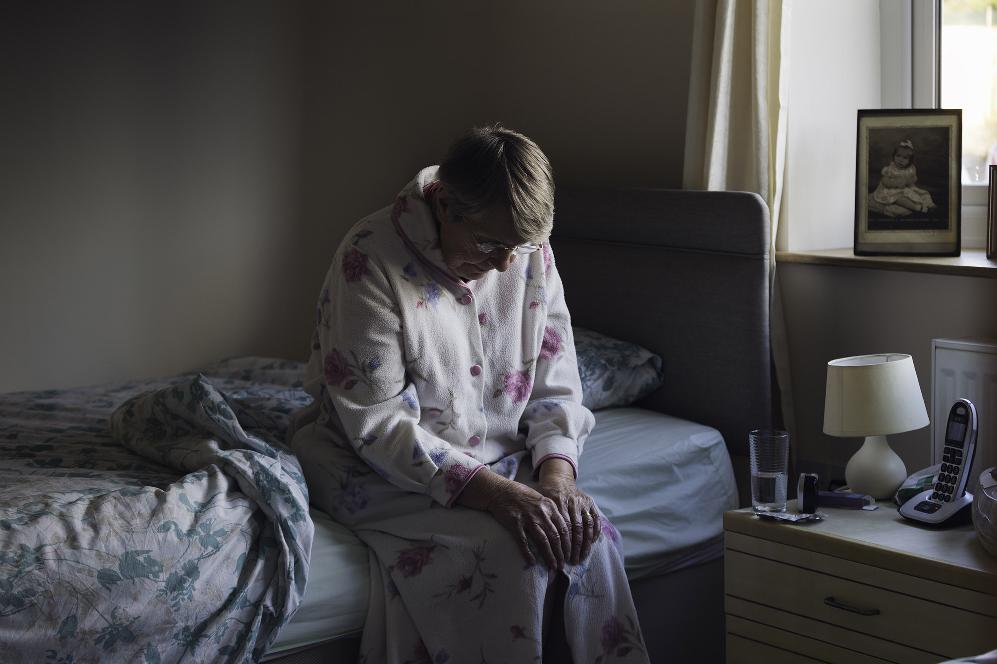 Depressed elderly woman sitting on a bed in the dark in a nursing home room