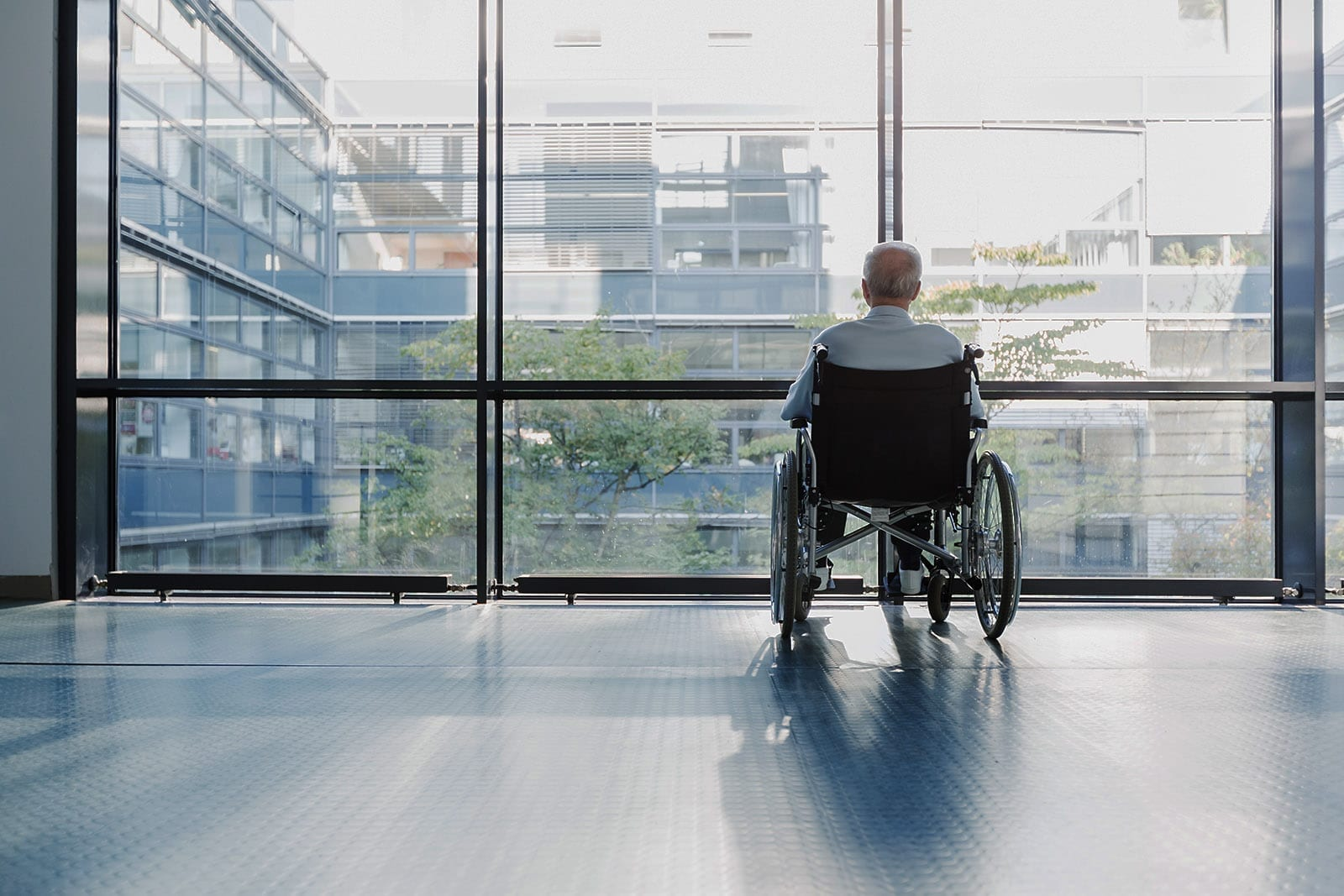 Senior Man in Wheelchair Looking Out Window