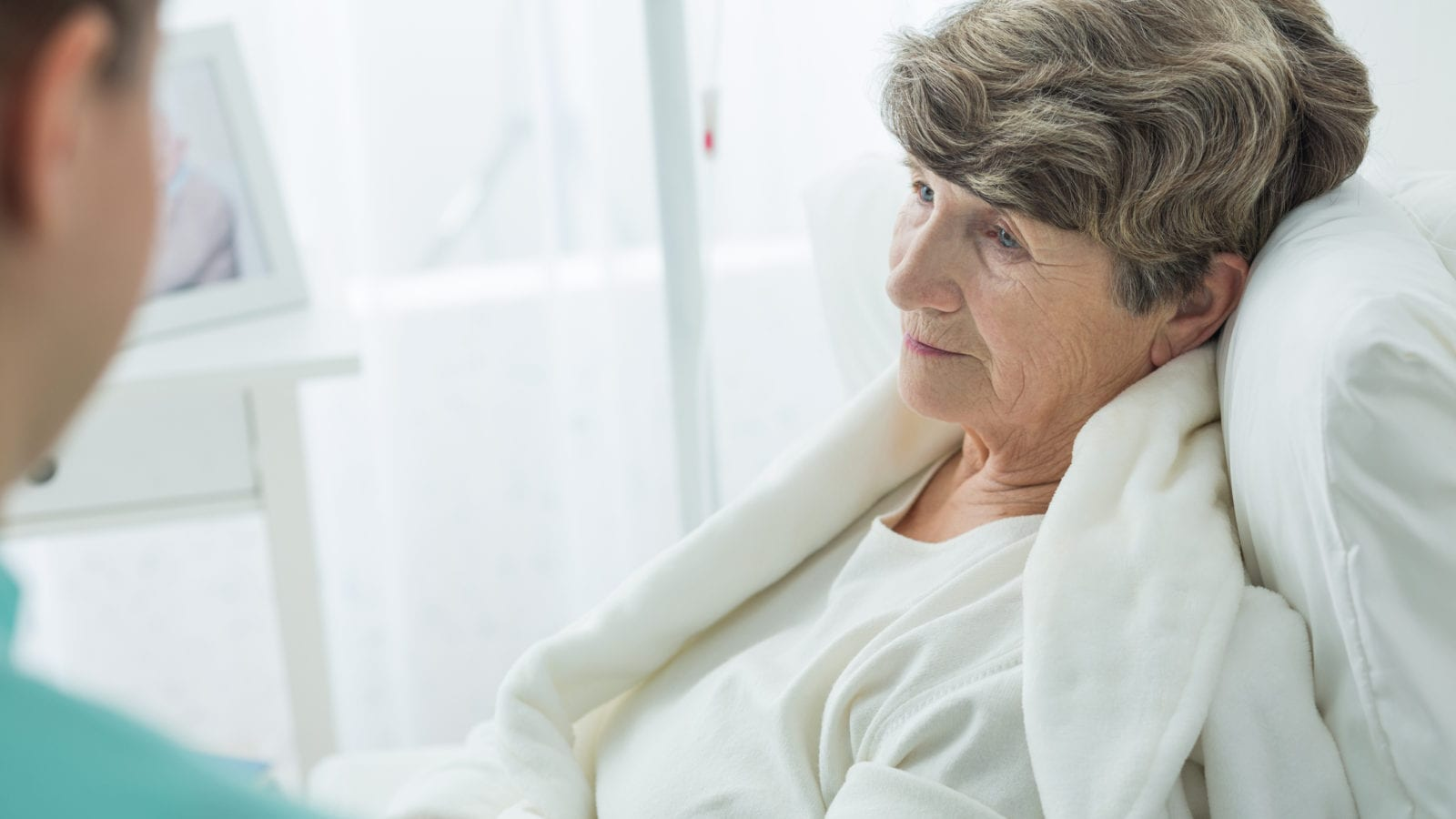 Photo of nurse and sad old woman at hospital