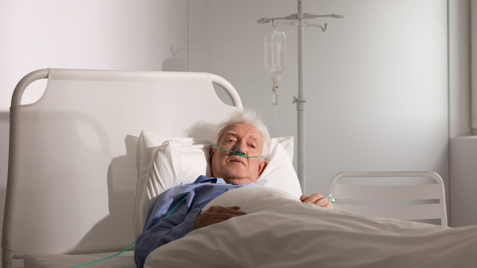 Elderly Man In A Nursing Home Bed