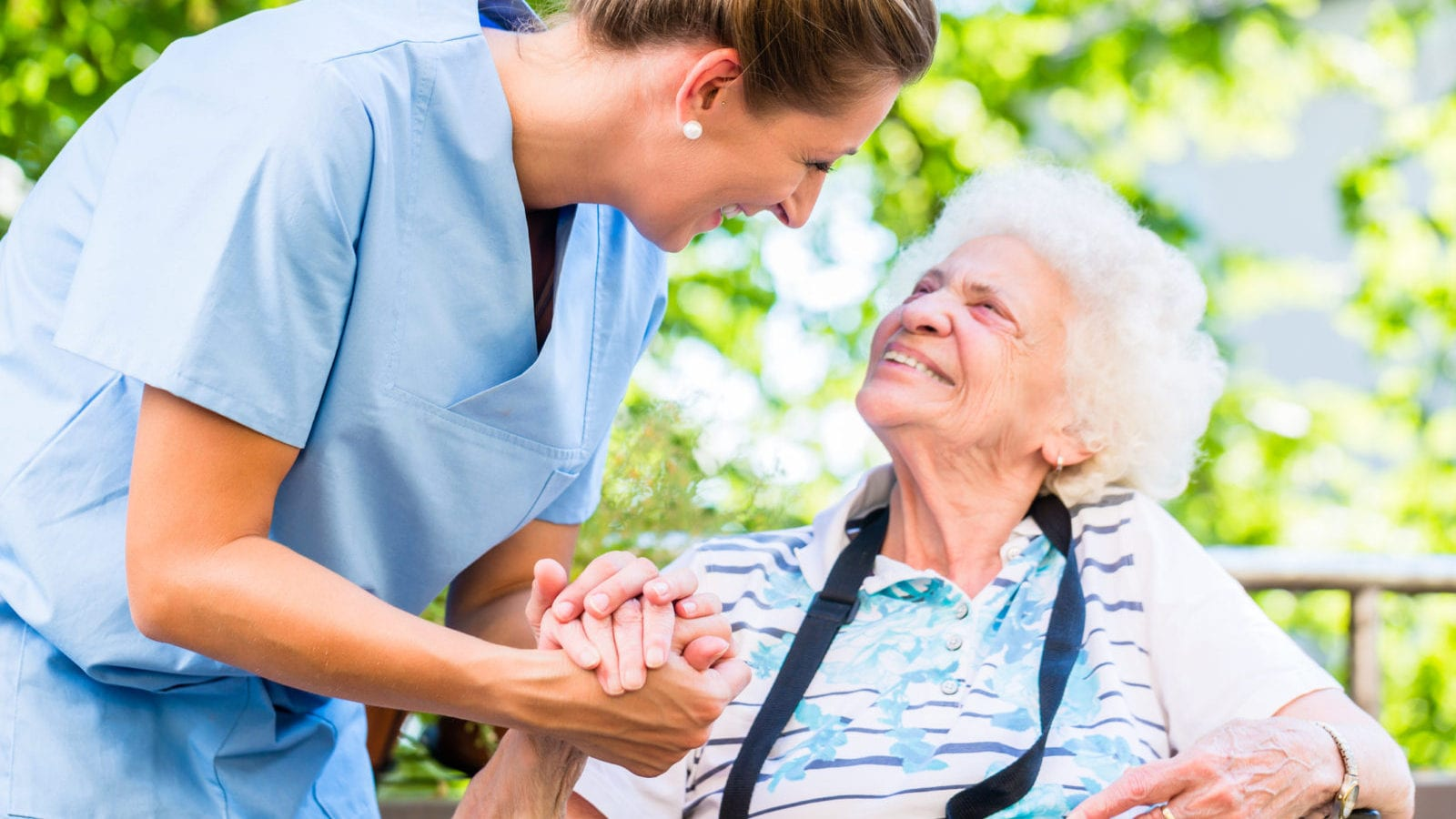 Nurse holding hand of senior woman in nursing home