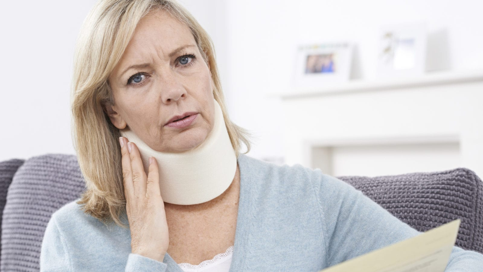 Mature Woman Reading Letter After Receiving Neck Injury