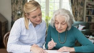 Mature Daughter Helping Elderly Mother With Paperwork