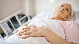 Elder Woman In Hospital Bed Stock Photo