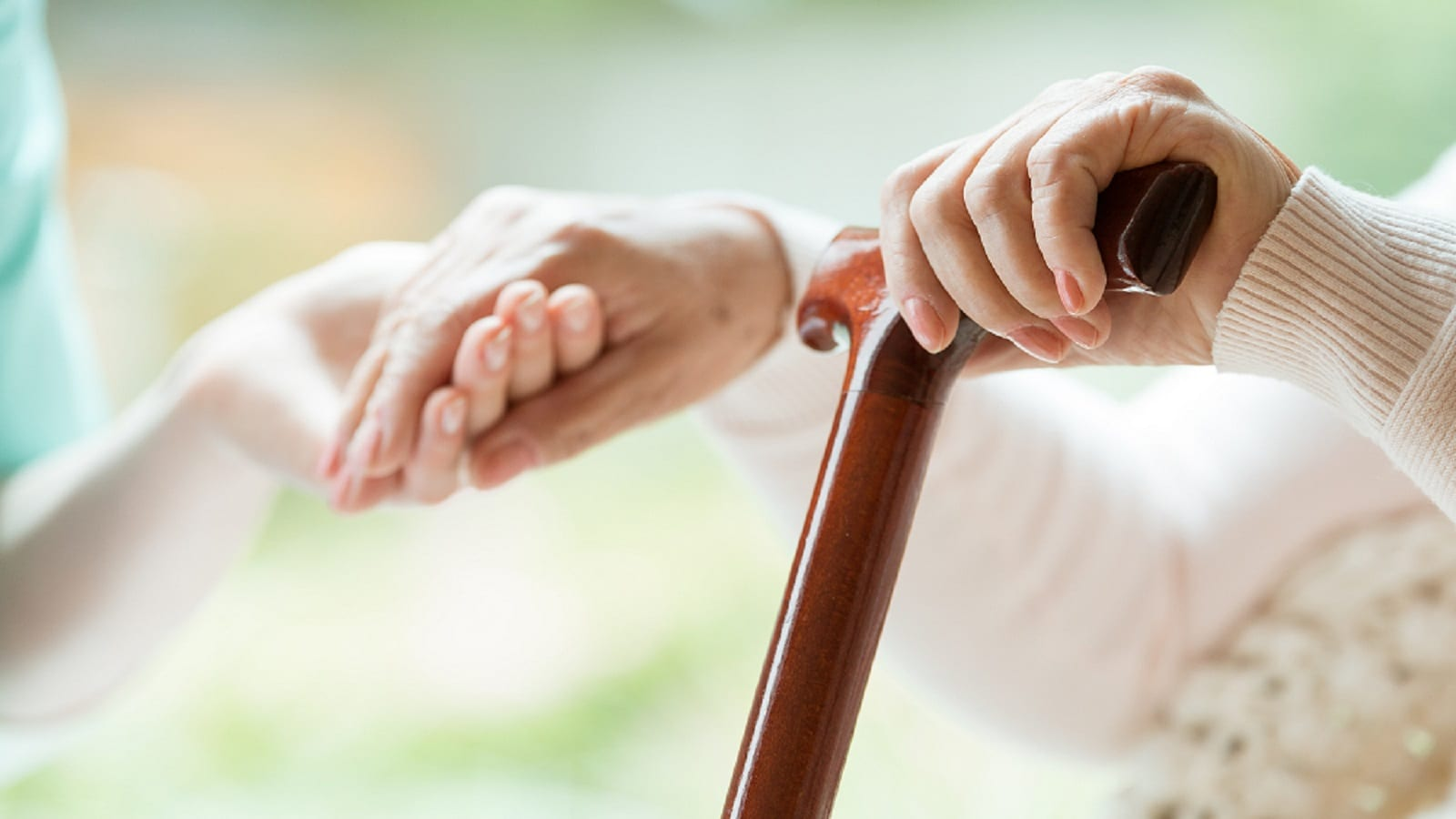 Nurse Helping Elderly Woman With Cane Stock Photo