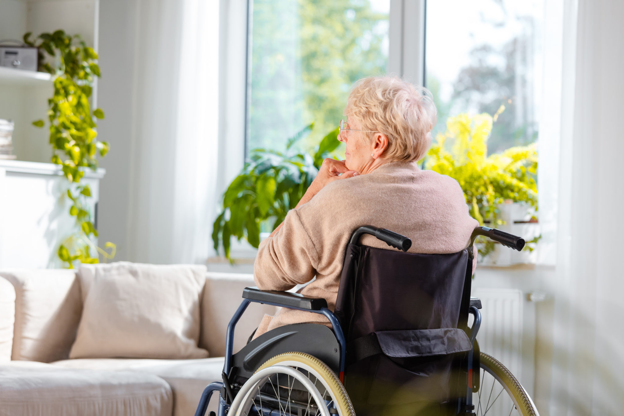 Lonely senior woman sitting in wheelchair in her house
