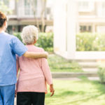 caregiver walking with elderly woman outdoor