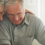a senior couple comforting each other in their Charleston, WV, nursing home facility