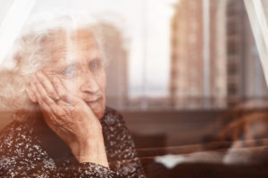 A Charleston, WV, nursing home resident looking out the window of her room