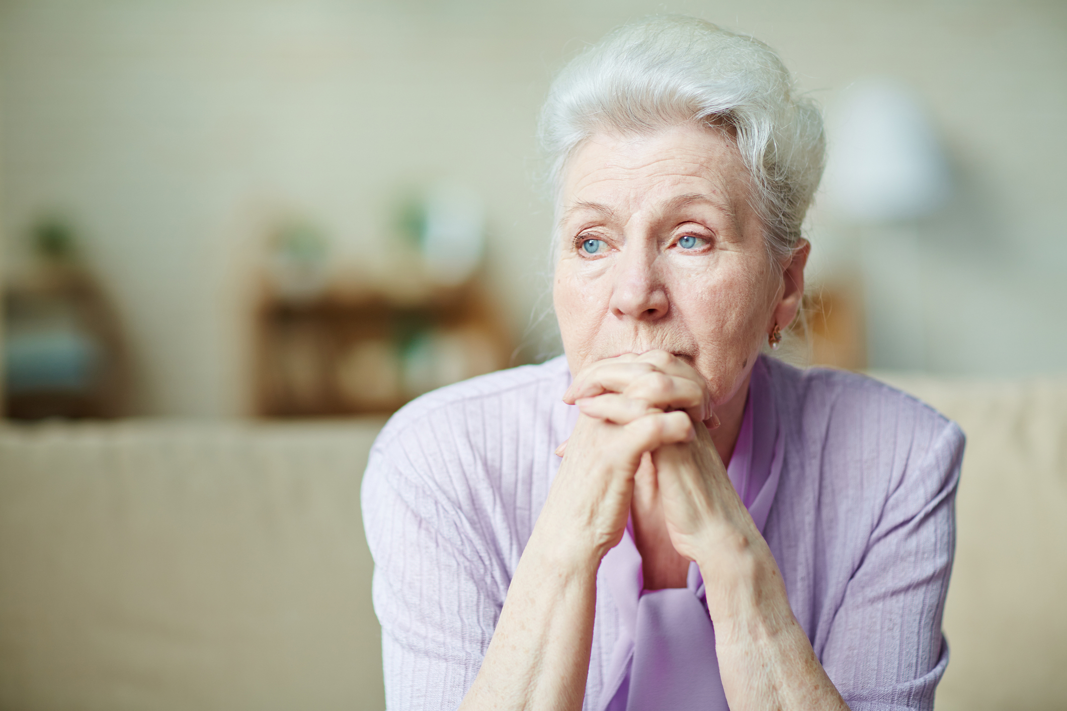 An older woman looking depressed after suffering elder abuse.
